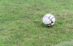 Old soccer ball on the grass of football field Royalty Free Stock Photography
