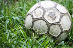 Old soccer ball in the grass on a rainy Royalty Free Stock Images