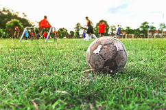 Old soccer ball on green grass field Stock Photography
