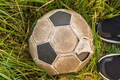 Old Soccer ball on the green grass, top view.  stock photos