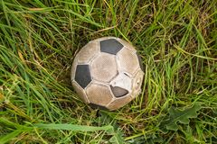 Old Soccer ball on the green grass, top view.  royalty free stock photos