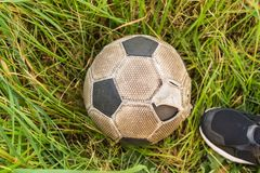 Old Soccer ball on the green grass, top view royalty free stock image