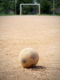 An old soccer ball on ground. Goal is the background Stock Photography