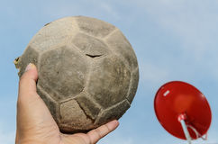 Old soccer ball in hand and red satellite background Royalty Free Stock Photography