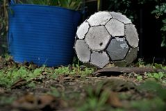 Old soccer ball lay on grass. Close up of worn out football. Torn up old soccer ball lay on grass. Worn out football. Concept of inactive person or useless royalty free stock photo
