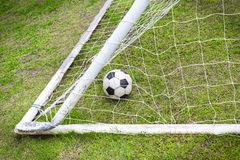 Old soccer ball in old goal net Stock Image