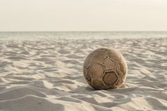 Old worn soccer ball on the beach stock image