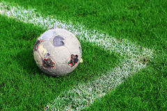 Old soccer ball on soccer field Royalty Free Stock Image