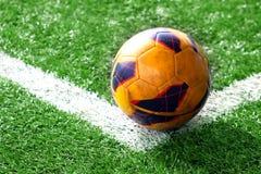 Old soccer ball on soccer field Stock Photos