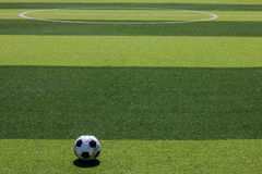 The old soccer football on the white line in the artificial turf Royalty Free Stock Image