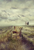 Old sofa chair in tall grass on path. Old sofa chair in tall grass on prairie path Royalty Free Stock Images