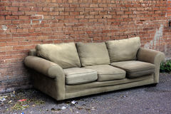 Old sofa discarded in an alley. Surrounded by trash and broken glass, against red brick wall Royalty Free Stock Photos