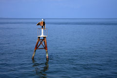 Old solar beacon in sea Stock Photography
