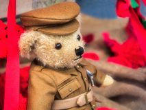 Old Soldier Remembrance Teddy. Golden-orange teddybear dressed in a soldier uniform surrounded by red poppies