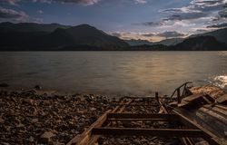 Old solitary boat wood destroyed aground in a lonely beach lake. Mountains view royalty free stock photography