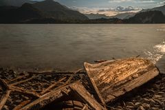 Old solitary boat wood destroyed aground in a lonely beach. Lake como stock image