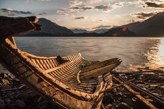 Old solitary boat wood destroyed aground in a lonely beach. Lake sunset stock photos