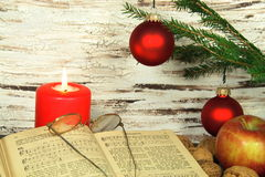 Old songbook, christmas decoration and candle. Christmas decoration with old songbook, glasses, nuts and red candle stock photo