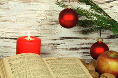Old songbook, christmas decoration and candle. Christmas decoration with old songbook, nuts and red candle royalty free stock image