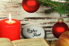 Old songbook, christmas decoration and candle. Christmas decoration with old songbook, nuts and red candle. Stone with the German words Frohes Fest (Happy stock images