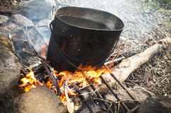 Old sooty black pan on a bonfire. Old sooty black pan with boiling water stands on a bonfire Stock Images