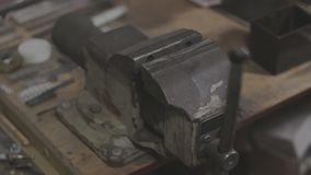 Old soviet mechanics bench vices are pressing the bottle cap stock video footage