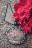 The Old Soviet Medal For Bravery of the Second World War with a red carnation, Victory Day May 9 postcard concept. Toned vintage Royalty Free Stock Images