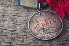The Old Soviet Medal For Bravery of the Second World War with a red carnation, Victory Day May 9 postcard concept. Toned vintage Royalty Free Stock Photography