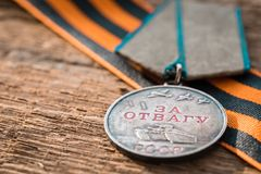 The Old Soviet Medal For Bravery of the Second World War with a red carnation, Victory Day May 9 postcard concept. Toned vintage Stock Photography