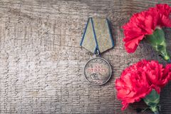 The Old Soviet Medal For Bravery of the Second World War with a red carnation, Victory Day May 9 postcard concept. Toned vintage Stock Photos