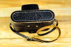 Old soviet rangefinder camera in leather case ona wooden table Stock Image