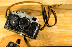 Old soviet rangefinder camera in leather case ona wooden table Royalty Free Stock Images
