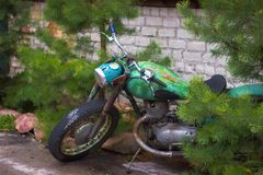 Old Soviet-style motorcycle covered with rust. Standing near a fence with coniferous trees Royalty Free Stock Images