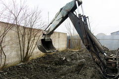 An old Soviet tractor digs and loads waste stone processing Stock Photo