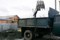 An old Soviet tractor digs and loads waste stone processing Stock Photography