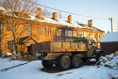 The old Soviet truck ZIL-157 at the abandoned wooden house in beams setting the sun. Russia stock photography