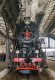Old Soviet vintage black retro train with a red star at the railway station in Lviv produces steam from the pipes and the passeng Royalty Free Stock Images