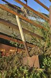 Old spade leans on a cattle loading chute Royalty Free Stock Image