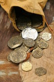 Old spanish coins. Spilling out of a Leather vintage money Bag on to cowhide Stock Image