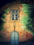 An old Spanish courtyard with a window and an old door. 07.12.2014.Spain Madrid.An old Spanish courtyard with a window and an old door. A growing tree and an stock photos