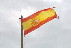 Old Spanish flag on a pole, undulating in the wind with clouds at the background, Santa Barbara castle of Alicante Royalty Free Stock Image