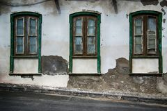 Old Spanish weathered windows. Set in weathered wall full of texture royalty free stock photo