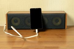 Old speaker linked by usb-cable to smartphone.  royalty free stock image