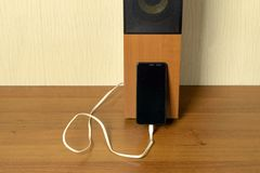 Old speaker linked by usb-cable to smartphone. Clouse-up. Old speaker linked by usb-cable to smartphone royalty free stock image