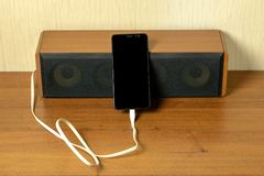 Old speaker linked by usb-cable to smartphone. Progress technology concept royalty free stock photo