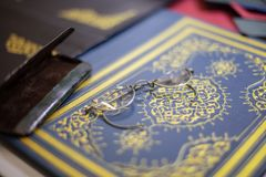 Old spectacles on bespoke book cover. Close up of bespoke book covers and old spectacles at a book binder royalty free stock images