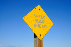 Old speed bump sign. A old corroded yellow speed bump warning sign Stock Photo
