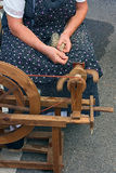 Old spinning wheel. Woman making thread with an old spinning wheel - old time method of spinning wool into yarn Stock Photography