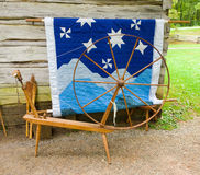 An old spinning wheel and a quilt on display at an historic site in virginia Stock Images