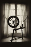 Old Spinning Wheel in Window Well Royalty Free Stock Photo